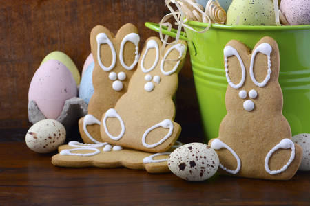 speckled wood: Happy Easter gingerbread cookie bunnies with bucket of speckled Easter eggs on dark wood grain background.