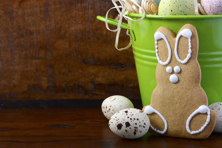 speckled wood: Happy Easter gingerbread cookie bunnies with bucket of speckled Easter eggs on dark wood grain background, with copy space. Stock Photo