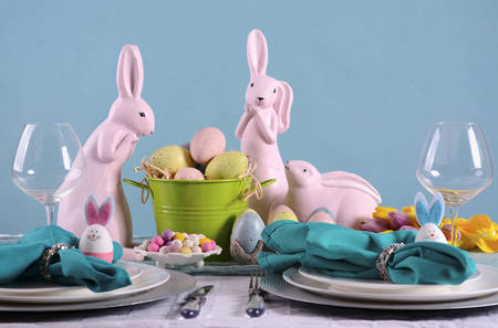 Happy Easter table setting with bunny and eggs centerpiece in pastel Spring color theme.