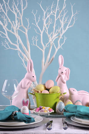 centerpiece: Happy Easter table setting with bunny and eggs centerpiece in pastel Spring color theme. Stock Photo