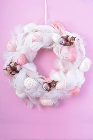 robin bird: Pretty pink and white Easter door wall hanging wreath with eggs, feathers and robin bird decorations on a pink wood background, vertical.