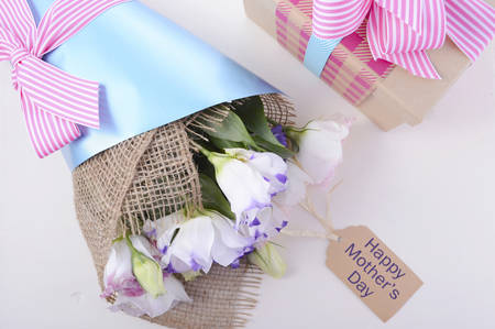 fondo blanco: Beautiful Mothers Day lisianthus flowers wrapped in burlap and blue paper with gift box on white wood table and blue background, overhead.