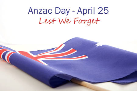 ANZAC Day, Lest We Forget, text with Australian Folded Flag on white wood table.
