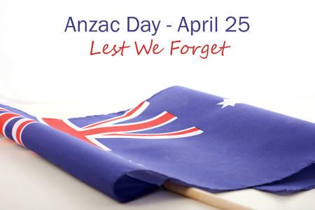 澳纽军团日,以免我们忘记,文本与澳大利亚折叠国旗在白色的木头桌子上。