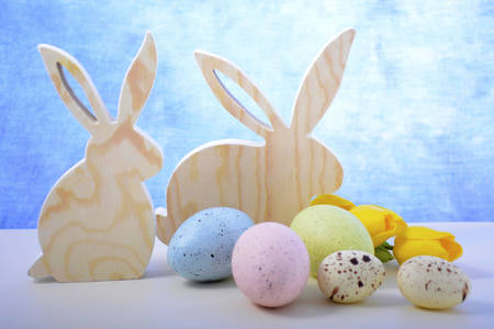 speckled wood: Happy Easter Wooden Bunnies with speckled eggs on white wood table and blue background.
