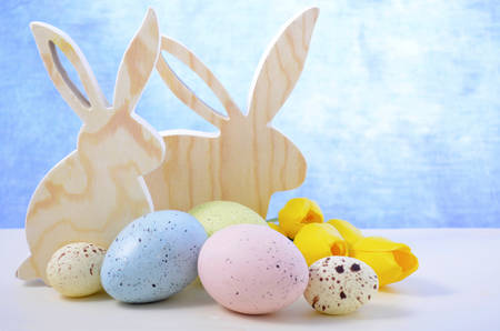 speckled wood: Happy Easter Wooden Bunnies with speckled eggs on white wood table and blue background, with copy space. Stock Photo