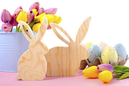 speckled wood: Happy Easter Wooden Bunnies with speckled eggs and spring tulips on a pink wood table .