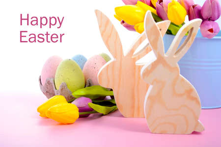 speckled wood: Happy Easter Wooden Bunnies with speckled eggs and spring tulips on a pink wood table, with copy space. Stock Photo
