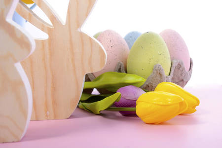 speckled wood: Happy Easter Wooden Bunnies with speckled eggs and spring tulips on a pink wood table, close up.