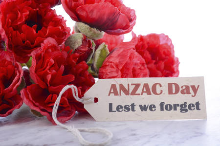 ww2: ANZAC Day, April 25, greeting with Lest We Forget and bunch of red silk poppies on white marble table.