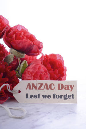 anzac: ANZAC Day, April 25, greeting with Lest We Forget and bunch of red silk poppies on white marble table.