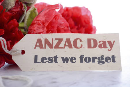 remembrance: ANZAC Day, April 25, greeting with Lest We Forget and bunch of red silk poppies on white marble table, closeup.