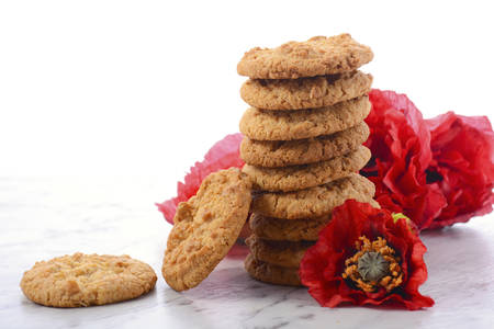 biscuit: ANZAC Day, April 25, traditional Anzac biscuits on white marble table with red poppies. Stock Photo