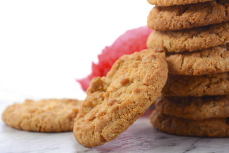 remembrance day poppy: ANZAC Day, April 25, traditional Anzac biscuits on white marble table with red poppies, closeup. Stock Photo
