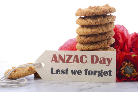 ANZAC Day, April 25, traditional Anzac biscuits on white marble table with red poppies. Stock Photo