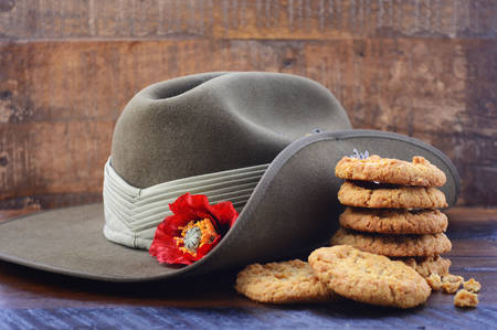 Anzac Day Australian Army slouch hat with stack of traditional Anzac biscuits on dark vintage wood background, with copy space.