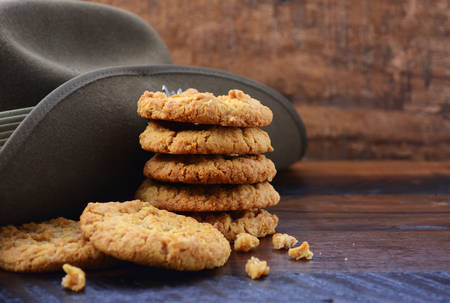 anzac: Anzac Day Australian Army slouch hat with stack of traditional Anzac biscuits on dark vintage wood background with copy space.