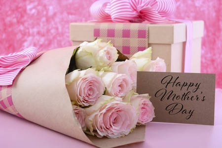 Happy Mothers Day gifts of pink roses and gift box wrapped in brown kraft paper on pink wood table, and greeting gift tag card.