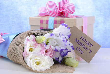 blue gift box: Beautiful Mothers Day lisianthus flowers wrapped in burlap and blue paper with gift box on white wood table and blue background, with gift tag.