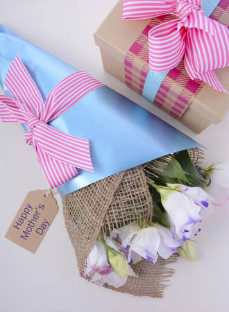 mothering: Beautiful Mothers Day lisianthus flowers wrapped in burlap and blue paper with gift box on white wood table and blue background, overhead.