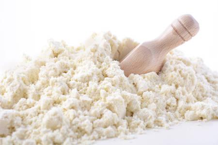Primo piano di polvere di proteine ??del siero con la paletta di legno su sfondo bianco di legno.