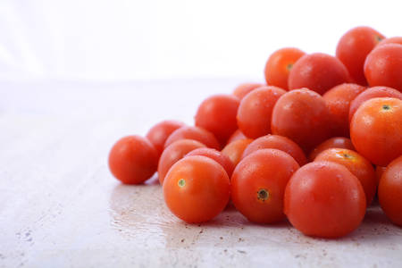 ripened: Pile of small red cherry tomatoes on white wood table background, with copy space. Stock Photo