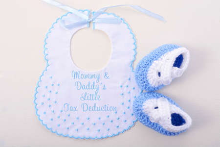 april 15: Babys bib on white wood background, with Tax Day message, Mommy and Daddys Little Tax Deduction. Stock Photo