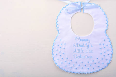 exemption: Babys bib on white wood background, with Tax Day message, Mommy and Daddys Little Tax Deduction, with copy space.