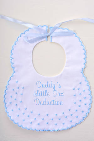 deduction: Babys bib on white wood background, with Tax Day message, Mommy and Daddys Little Tax Deduction. Stock Photo