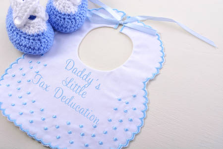 deduction: Babys bib on white wood background, with Tax Day message, Mommy and Daddys Little Tax Deduction, closeup.