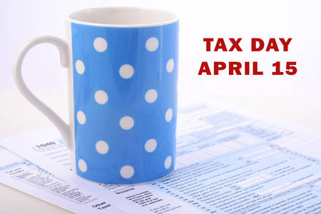day break: USA Tax Day, April 15, coffee break with tax return and coffee mug, with copy space.
