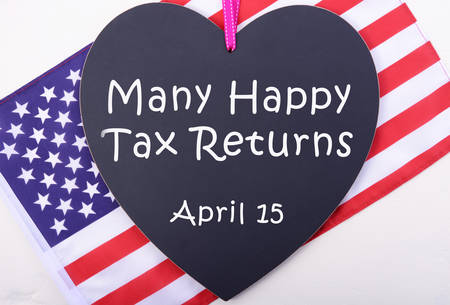 april 15: Many Happy Tax Returns message on heart shaped blackboard with USA Stars and Stripes flag for Tax Day, April 15.