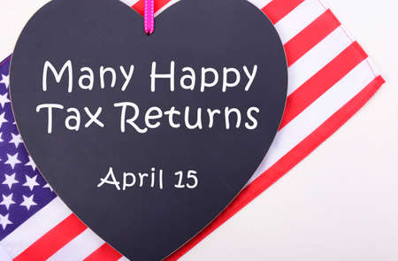 exemption: Many Happy Tax Returns message on heart shaped blackboard with USA Stars and Stripes flag for Tax Day, April 15, with additional copy space.