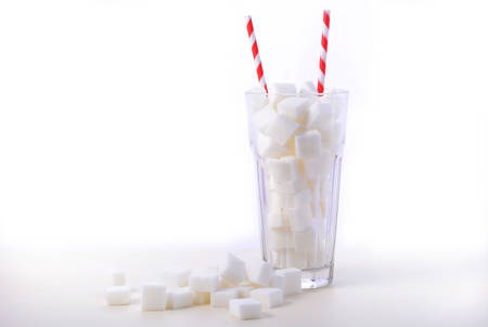 Soda glass of white sugar cubes with red and white straws on white wooden table