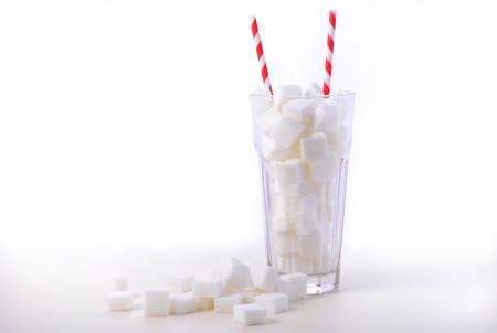 Vidrio de sosa de terrones de azúcar blanco con la paja rojas y blancas en mesa de madera blanca Foto de archivo - 55147392