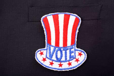 uncle sam hat: Closeup of USA vote badge in shape of Uncle Sam hat on black suit jacket pocket.