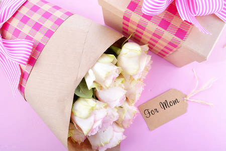 mothering: Happy Mothers Day gifts of pink roses and gift box wrapped in brown kraft paper on pink wood table.