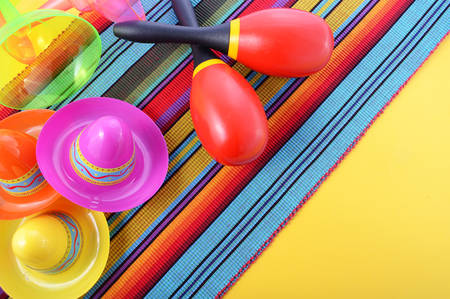 vibrant background: Vibrant Cinco de Mayo background with sombrero hats and maracas on bright festive background. Stock Photo