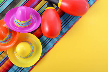 mexicana: Vibrant Cinco de Mayo background with sombrero hats and maracas on bright festive background, with copy space.