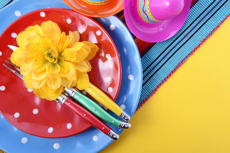 Vibrant Cinco de Mayo table place setting on bright festive background with copy space. Stock Photo