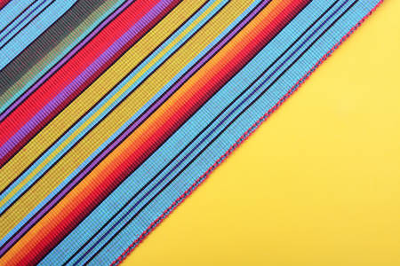 5th: Cinco de Mayo festive stripe material on yellow background, with copy space. Stock Photo