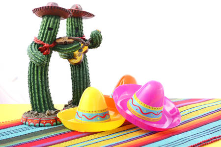 mexicana: Cinco de Mayo Mariachi Band cactus with sombero hats on festive table with white background, and copy space.