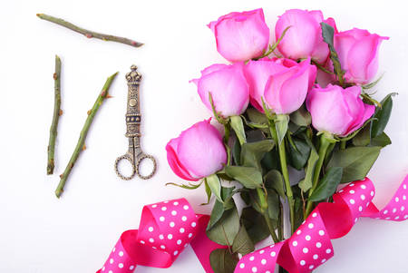 mothering: Trimming bouquet of pink roses with antique scissors on white wood table.