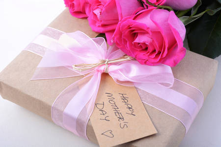 mothering: Happy Mothers Day brown paper gift and pink roses on white wood table, closeup.