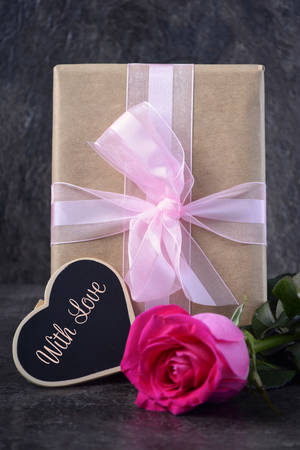 mothering: Mothers Day gift with pink rose and greeting on black slate background.