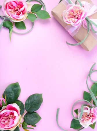 feminine background: Pale pink feminine background with gift and silk roses on wood table with decorated borders, for Mothers Day, Valentine or feminine birthday or anniversary with copy space. Stock Photo