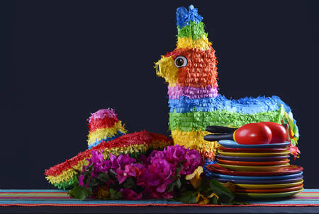 Colorful Happy Cinco de Mayo party table with rainbow straw donkey and sombrero pinata against a black background.