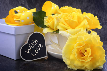 mothering: HAppy Mothers Day gift of yellow roses in vintage style china tea cup on black slate background. Stock Photo