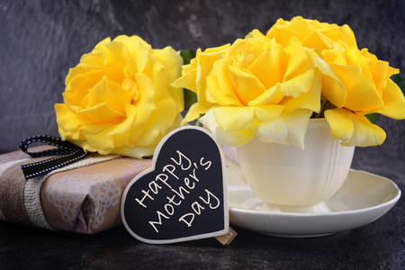 HAppy Mothers Day gift of yellow roses in vintage style china tea cup on black slate background. 스톡 콘텐츠