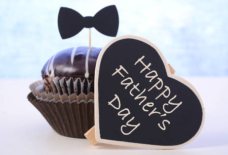 Happy Fathers Day cupcake gift on pale blue and white wood background. Standard-Bild